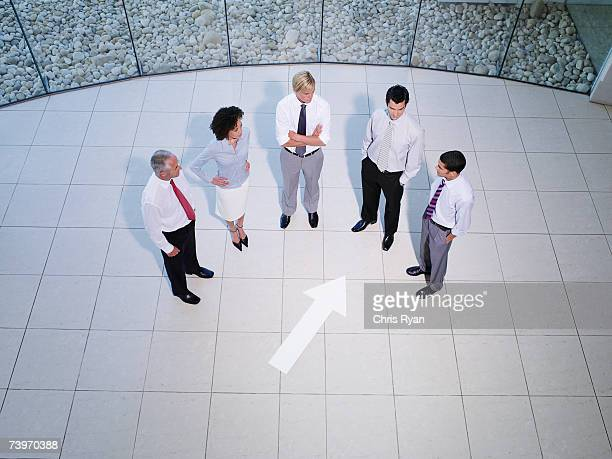 Aerial view of five office workers with pointing arrow sign on floor