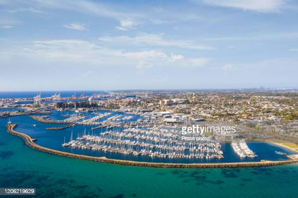 aerial view of fremantle harbor with sailboat and yacht mooring in harbor at bay with container port terminal and city in background in perth, western australia, australia. - フリーマントル ストックフォトと画像