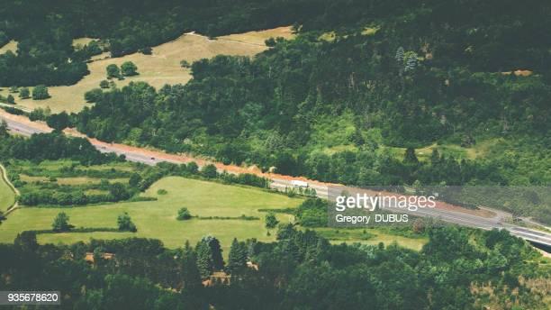 flygfoto över franska landsväg väg passerar lummiga lövverk grön skog under sommarsäsongen - ain bildbanksfoton och bilder