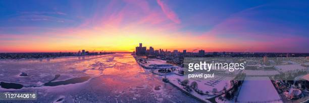 aerial view of frozen detroit river with city skyline in winter - detroit michigan stock pictures, royalty-free photos & images