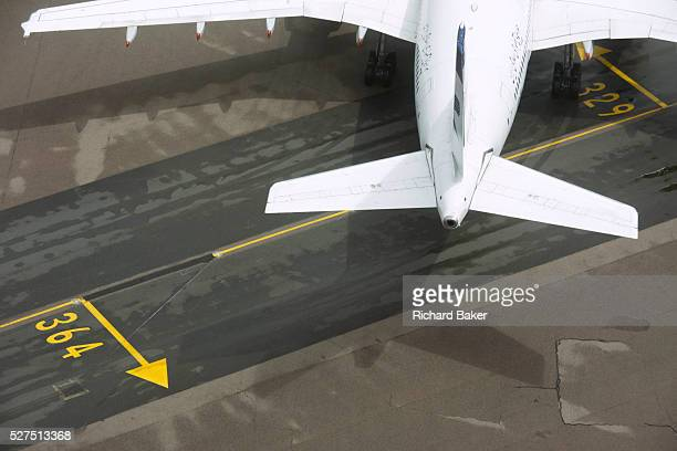 Aerial view of generic airliner at London Heathrow airport A generic airliner turns off a directional centreline that helps pilots navigate to...