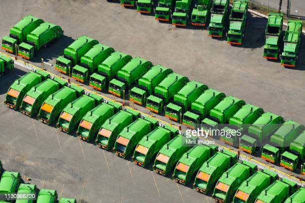 aerial view of green garbage trucks in a row in parking lot - garbage truck stock pictures, royalty-free photos & images