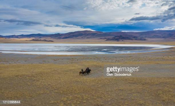 aerial view of group of eagle hunters near the river in mongolia - nomadic people stock pictures, royalty-free photos & images