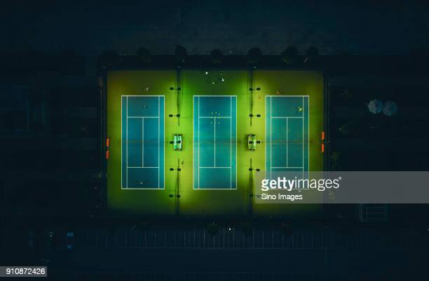 aerial view of group of people playing tennis on illuminated tennis courts at night, shanghai, china - image stock pictures, royalty-free photos & images