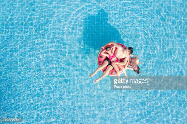 aerial view of happy asianfamily in the pool, having fun in the water, father, mother with daughter enjoying aqua park in resort, summer holidays, vacation concept - station de vacances photos et images de collection