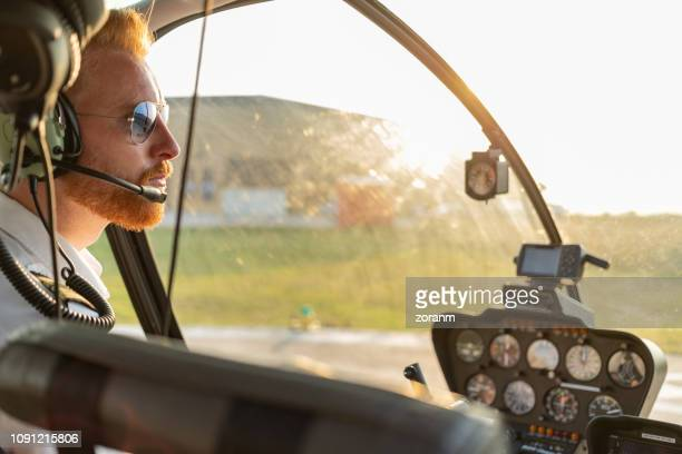 aerial view of helicopter pilot welcoming passengers - piloting stock pictures, royalty-free photos & images