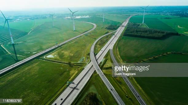 aerial view of highways by wind turbines on field, berlin, brandenburg, germany - umweltschutz stock-fotos und bilder