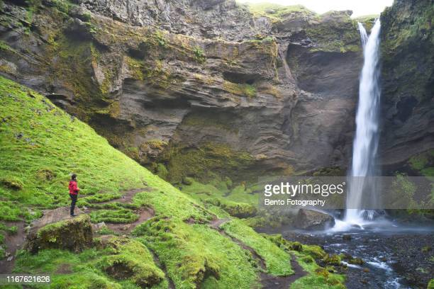 aerial view of hiker at majestic kvernufoss waterfall in iceland - 峡谷 ストックフォトと画像