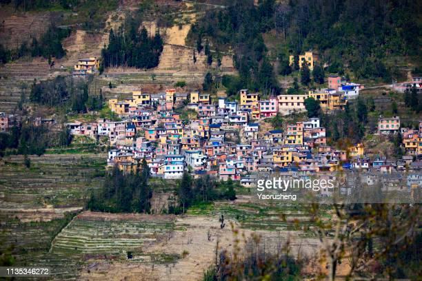 aerial view of historic indigenous village surrounded by rice terraces at yuanyang,yunnan province,china - yuanyang imagens e fotografias de stock