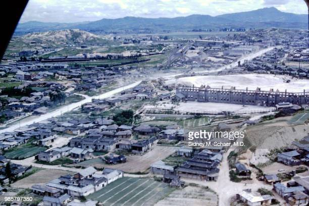 Aerial view of homes small fields a large factory and train lines Seoul South Korea July 1952