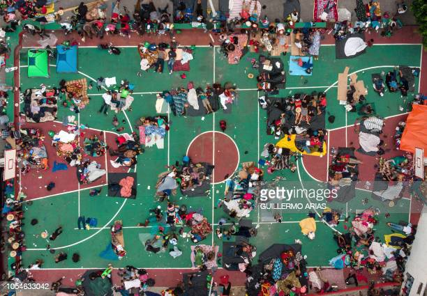 TOPSHOT Aerial view of Honduran migrants heading in a caravan to the US resting in a basketball pitch in San Pedro Tapanatepec Oaxaca state southern...