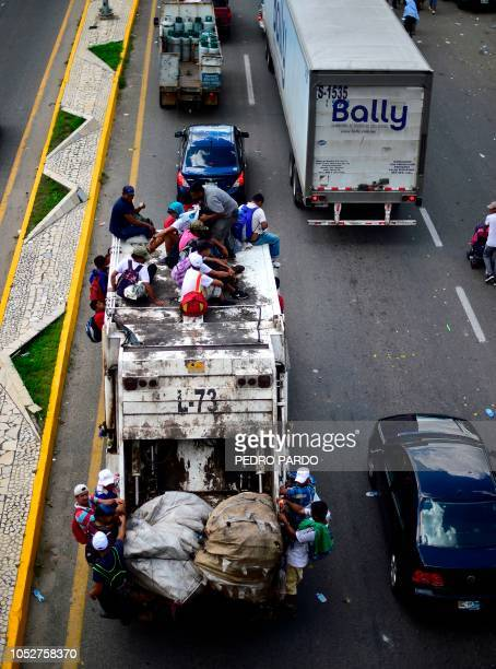 Aerial view of Honduran migrants onboard a garbage truck as they take part in a caravan heading to the US in the outskirts of Tapachula on their way...