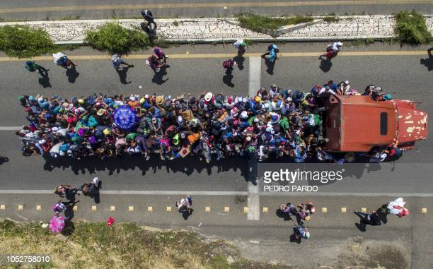 TOPSHOT Aerial view of Honduran migrants onboard a truck as they take part in a caravan heading to the US in the outskirts of Tapachula on their way...