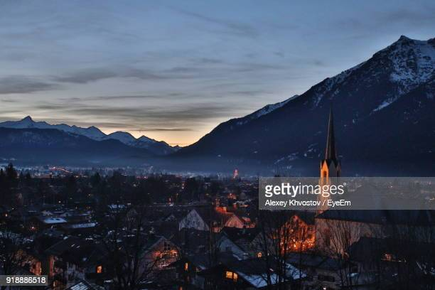 aerial view of houses and mountains during winter at night - garmisch partenkirchen stock pictures, royalty-free photos & images