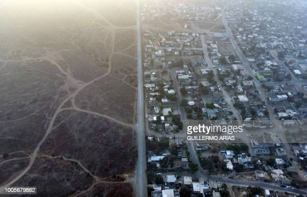 TOPSHOT Aerial view of houses and structures sitting right next to the MexicoUS border fence at El Nido de las Aguilas in eastern Tijuana Baja...