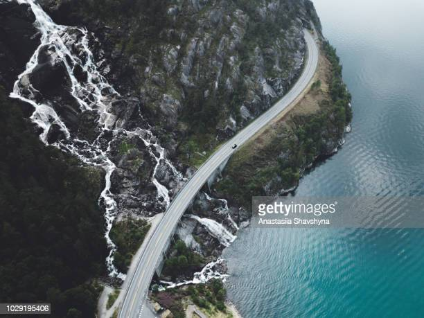 aerial view of huge waterfall falling into the turquoise lake and road in norway - road stock pictures, royalty-free photos & images