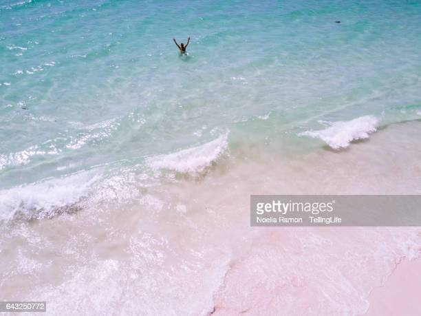 Aerial view of Hyams Beach with one man in the water waving at the camera, Jervis Bay, Australia