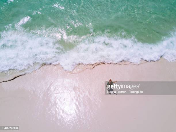 Aerial view of Hyams Beach with one woman at the shore waving at the camera, Jervis Bay, Australia