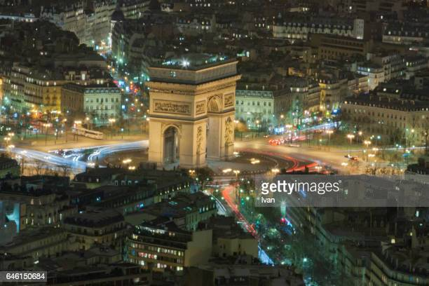 aerial view of illuminated arc de triomphe in city at night - place charles de gaulle paris stock photos and pictures
