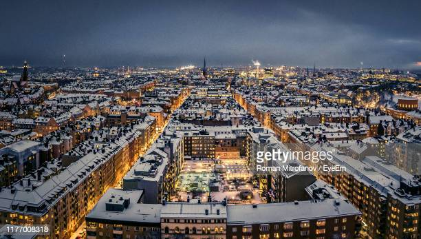 aerial view of illuminated buildings in city against sky at night - stockholm stock pictures, royalty-free photos & images