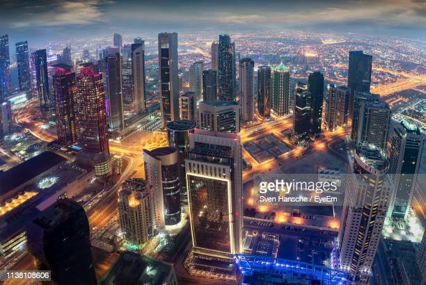 aerial view of illuminated buildings in city at night - doha photos et images de collection