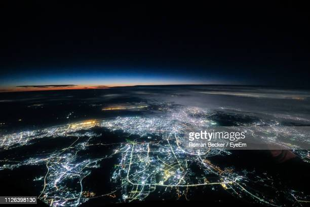 aerial view of illuminated city against sky at night - satellite view stock pictures, royalty-free photos & images