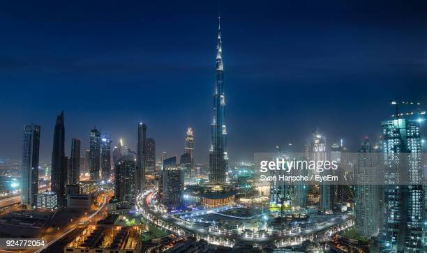 aerial view of illuminated city at night - burj khalifa stock photos and pictures