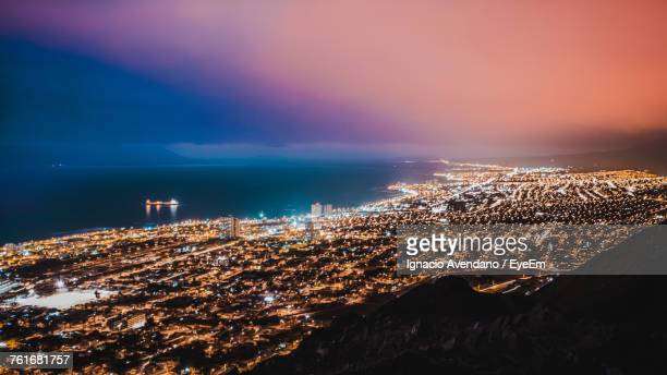 aerial view of illuminated city by sea against sky at sunset - antofagasta region stock photos and pictures