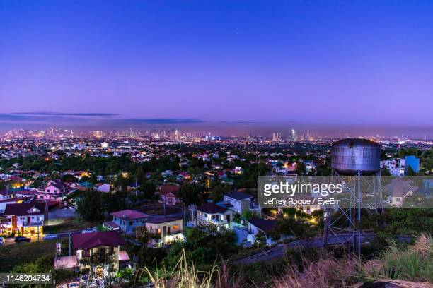 aerial view of illuminated cityscape against blue sky at dusk - jeffrey roque stock photos and pictures