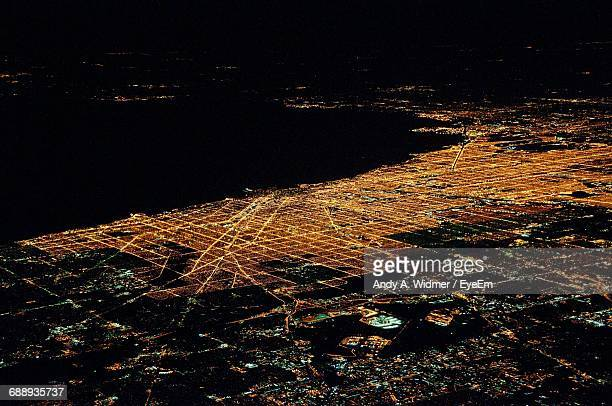 Aerial View Of Illuminated Cityscape By River At Night