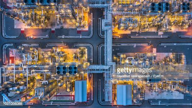 aerial view of illuminated factory in city at night - oil refinery stock pictures, royalty-free photos & images