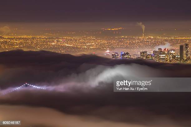 Aerial View Of Illuminated Residential District And Clouds At Night