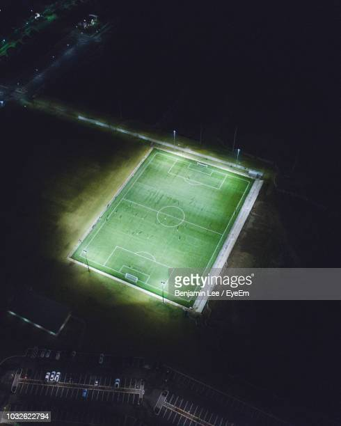 aerial view of illuminated soccer field at night - voetbalveld stockfoto's en -beelden