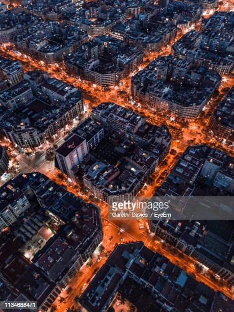 aerial view of illuminated street amidst buildings in city - barcelona spanien stock-fotos und bilder