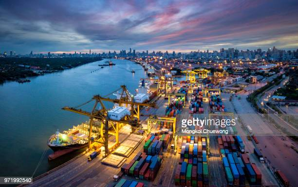 aerial view of international port with crane loading containers in import export business logistics with cityscape of bangkok city thailand at night - shipyard stock pictures, royalty-free photos & images