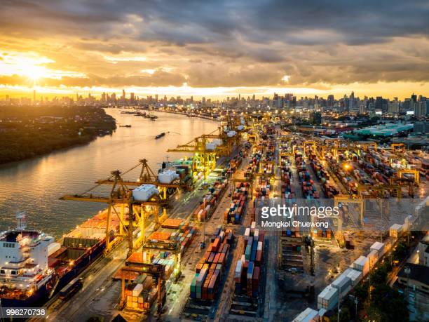 aerial view of international port with crane loading containers in import export business logistics with cityscape of modern city at sunset - commercial dock stock pictures, royalty-free photos & images