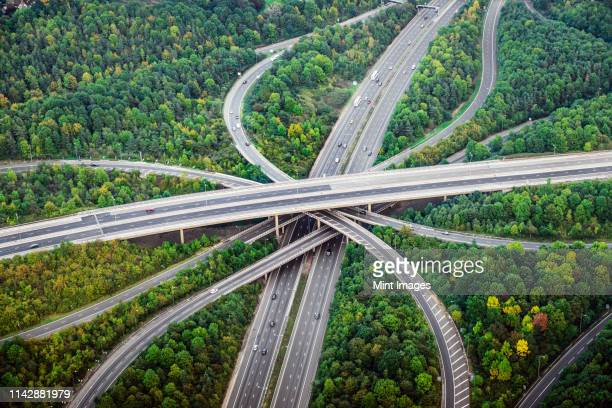 aerial view of intersecting highways near trees, london, england - flyover stock pictures, royalty-free photos & images