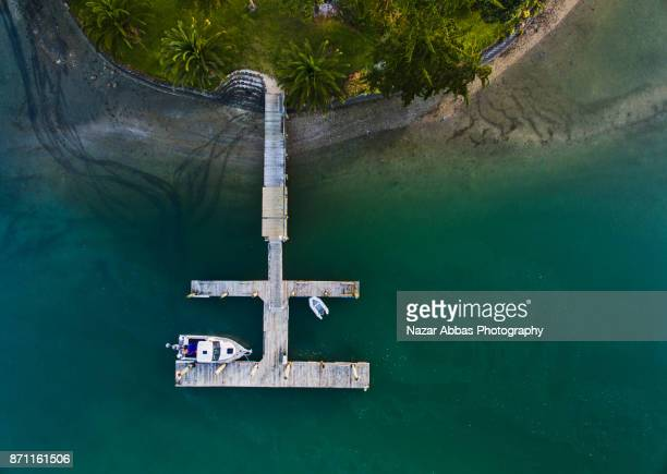 aerial view of jetty with boat parked. - ファンガパラオア半島 ストックフォトと画像