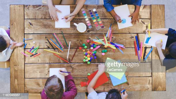 aerial view of kids doing arts and crafts - arti e mestieri foto e immagini stock