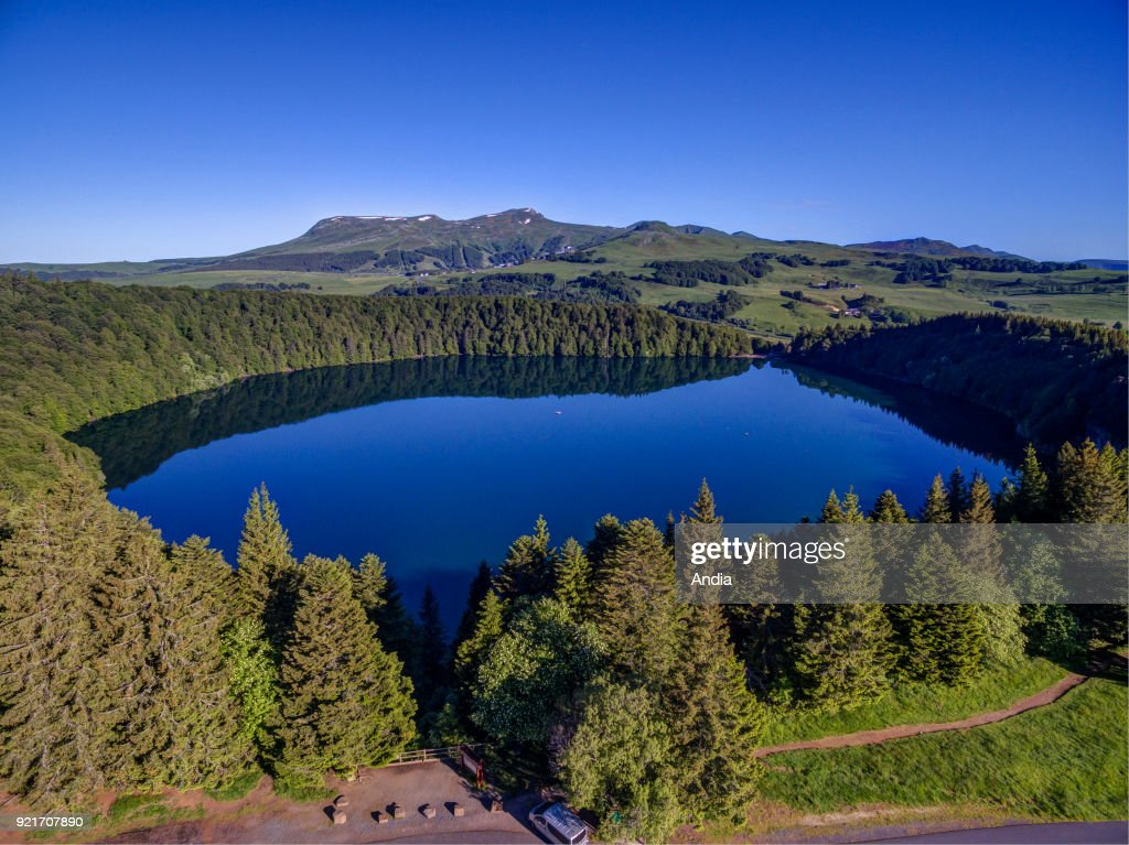 Aerial view of 'lac Pavin', a crater lake located in the Monts Dore mountain range in the Massif Central, Puy-de-Dome department, close to Besse-et-Saint-Anastaise. The crater lake and the surrounding mountains viewed from above.
