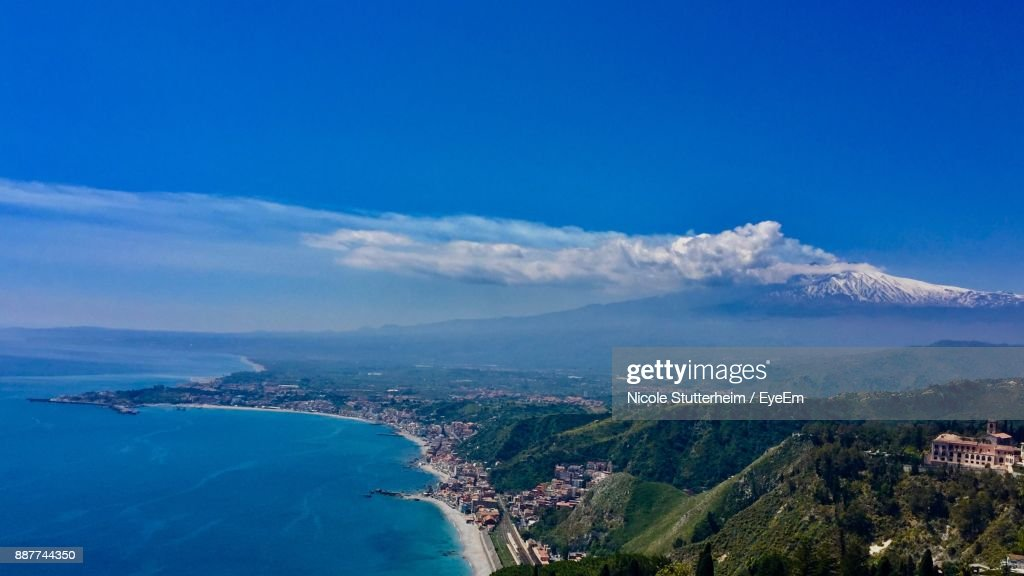 Aerial View Of Landscape And Sea Against Blue Sky : Stock Photo