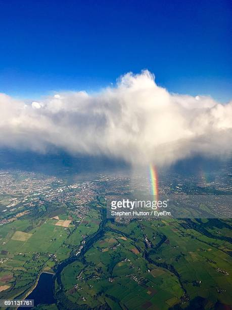 aerial view of landscape with rainbow against cloudy sky - hutton stock photos and pictures