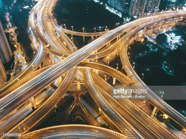aerial view of light trails on elevated roads at night - agilité photos et images de collection