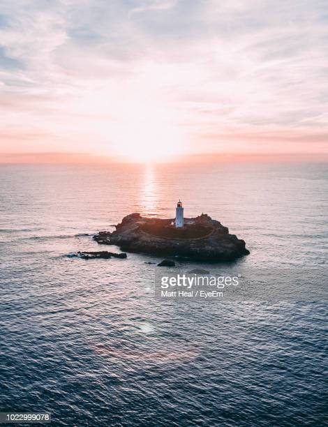 aerial view of lighthouse amidst sky during sunset - ファルマス ストックフォトと画像