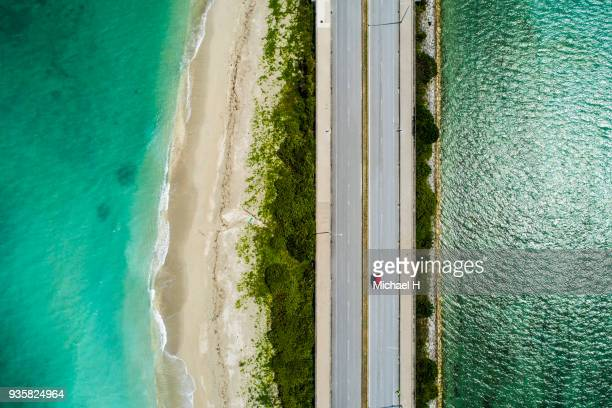 aerial view of linear road and blue sea. - asymmetry stock pictures, royalty-free photos & images
