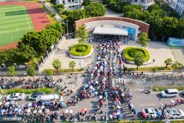 Aerial view of local residents queue up for COVID-19 nucleic acid testing at a primary school on September 14, 2021 in Xiamen, Fujian Province of...