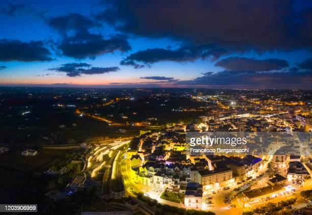 aerial view of locorotondo village at dusk with lights on. - italia stockfoto's en -beelden