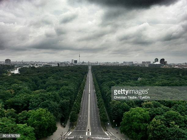 Aerial view of long highway between dense forests against cloudy sky