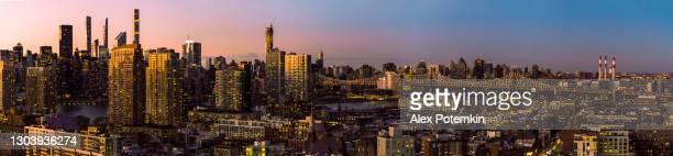 日没時にクイーンズボロ橋とルーズベルト島への住宅街の上に、ロングアイランドシティの空中写真。特大高解像度ステッチパノラマ。 - extra long ストックフォトと画像