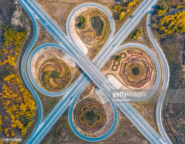aerial view of major motorway road intersection - symmetry stock pictures, royalty-free photos & images